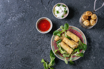 Fried spring rolls with red and white sauces, served in traditional china plate and fry basket with fresh green salad over black texture background. Flat lay, space. Asian food