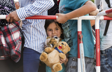 A girl holds a teddy bear as she stands among migrants outside the main railway station in Munich
