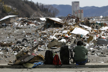 A survivor sits with belongings he found in the debris of his destroyed house in Yamada