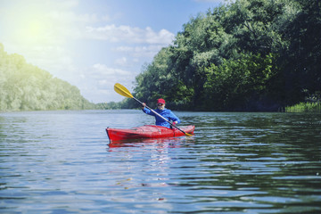 A girl rafts on a kayak on a river in a sunny day.