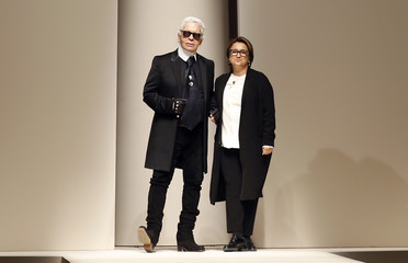 German designer Karl Lagerfeld and Italian designer Silvia Venturini Fendi acknowledge the crowd at the end of the presentation of Fendi's Autumn/Winter 2015/16 collection during Milan Fashion Week