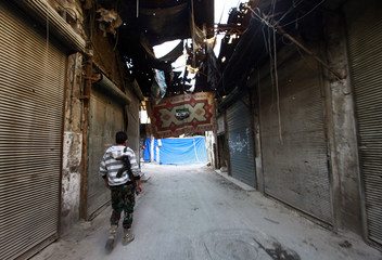 Free Syrian Army fighter walks in the old city of Aleppo