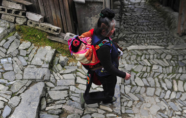 An ethnic Miao woman walks with a baby on her back on the first day of the Guzang Festival in Leishan county