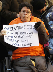 A woman in a wheelchair holds a placard during a protest of disabled people against cuts in social subsidies at the regional government in Valencia