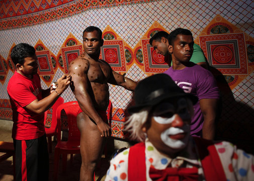 A competitor has tanning lotion applied on his body before his turn in a body building competition in Mumbai