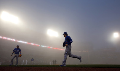 Toronto Blue Jays shortstop Kawasaki and center fielder Rasmus leave the field during a fog delay in the third inning against the Chicago White Sox during their MLB baseball game in Chicago