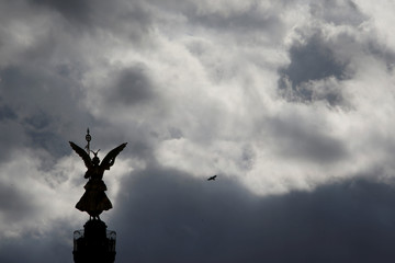 A bird flies beside the 'Golden Victoria' monument on top of the Siegessaeule (victory column) as it is silhouetted against a dark cloudy sky in Berlin