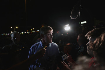 Missouri Attorney General Chris Koster stops to speak to reporters as demonstrators protest the shooting death of Michael Brown in Ferguson, Missouri