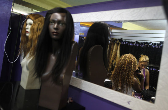 A woman buys hair extensions called Megahair, at a hair shop in a local market in Rio de Janeiro