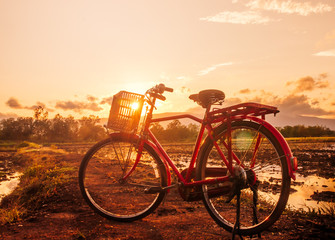 Beautiful landscape at sunset time with red classic bicycle