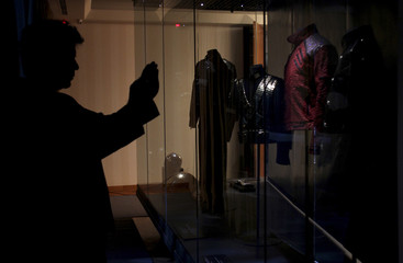 A man takes pictures of Michael Jackson's jackets during an exhibition at the Fashion Museum in Santiago