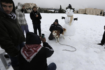 People take pictures of each other in the snow following a snowstorm at a park in Jerusalem