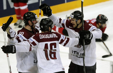 Latvia's Daugavins celebrates his goal against Switzerland with team mates Darzins and Redlihs during their Ice Hockey World Championship game at the O2 arena in Prague
