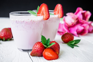Strawberry smoothie with fresh berries and pink flowers on white wood table and dark background. Fresh milkshake