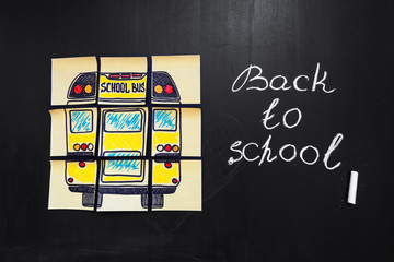 "Back to school background with title ""Back to school"" and ""school bus""  written on the yellow pieces of paper on the  chalkboard with title ""Back to school""  written by chalk"