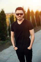 Young handsome man in sunglasses on the sunset