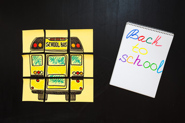 """Back to school background with title """"Back to school"""" and """"school bus"""" written on the yellow pieces of paper and notebook with title """"Back to school"""" are on the chalkboard"""