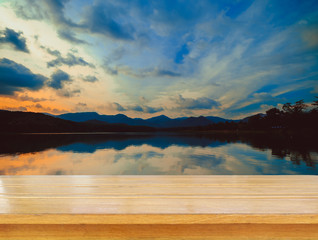 Empty top of wooden table and view of sunset or sunrise background