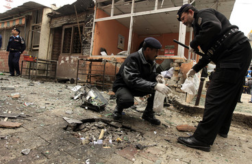 Policemen collect evidence from the site of a bomb attack at the district court in Islamabad