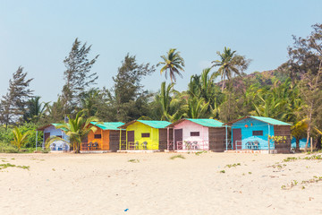 Palolym beach, colorful bungalows on the sea on the background of coconut palms, Goa, India.