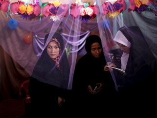 "Afghan women stand at a kiosk during inauguration of ""Spring of Holy Quran"" exhibition during the month of Ramadan, in Kabul"