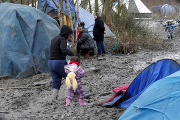 Migrants walk in a muddy field called the Grande-Synthe jungle, a camp of makeshift shelters where migrants and asylum seekers from Iraq, Kurdistan, Iran and Syria gather in Grande-Synthe, near Dunkerque