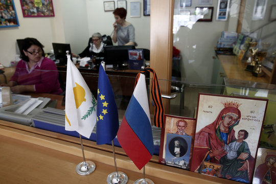 Employees of Vestnik Kipra weekly, a Russian newspaper, are seen working behind flags and Russian Orthodox religious icons at Limassol, a coastal town in southern Cyprus