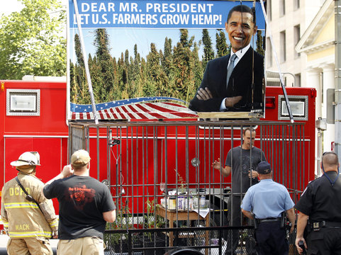 David Bronner talks to police as he stages a protest inside a steel cage, in front of the White House in Washington