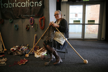 A woman knits with large knitting needles during the Knitting and Stitching show at Alexandra Palace in London