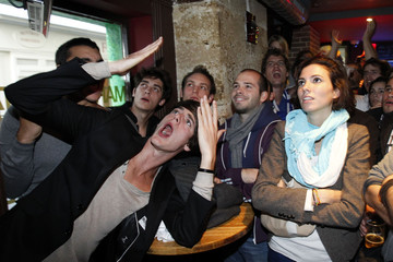France rugby team fans react as they watch a giant screen which displays the World Cup Rugby Final where New Zealand plays France, at a cafe in Paris