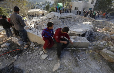 Palestinians look at the rubble of a Palestinain house that was demolished by Israeli troops in the village of Silwad near Ramallah