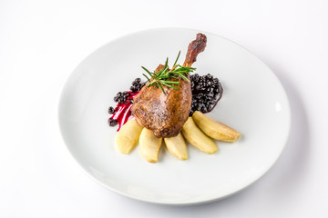 Duck leg baked with apples and currant sauce on white plate close-up view from above.