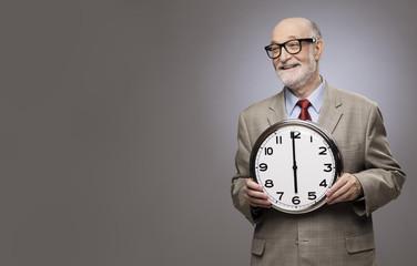 Senior man holding a big wall clock