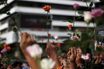 People hold flowers during a rally at the scene of Thursday's gun and bomb attack in central Jakarta