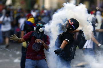 An anti-government protester throws a gas canister at the police during clashes at Altamira square in Caracas