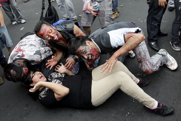 Men dressed as zombies pose for a photo during a Zombie Walk procession on the streets in Mexico City