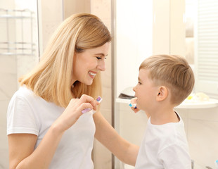 Beautiful mother and happy son brushing teeth near mirror in bathroom