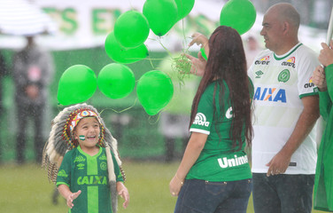 Carlinhos (L) represent the mascot Indian Conda of Chapecoense with his parents while paying tribute to the victims of the plane crash in Colombia at Arena Conda stadium in Chapeco