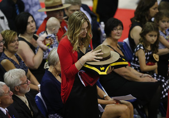 Rachael Vander Ploeg, the widow of RCMP Contanble Dave Ross, holds his hat and flag during a regimental funeral for three officers who were killed last week in Moncton