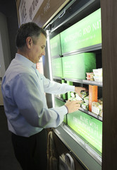 Starbucks president of global development Rubinfield arranges display of Evolution Fresh food products on display for sale bar in Bellevue