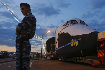 A police officer stands guard in front of a life-sized model of Soviet-made Buran space orbiter at VDNKh in Moscow