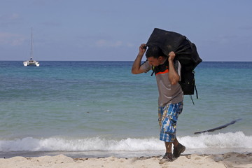 A cuban migrant arrives at the beach as he carries a bag on his back after crossing the border from Colombia through the jungle into La Miel, in the province of Guna Yala, Panama