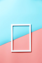 White picture frame on Two tone Pink and blue background.copy space,Top view,flat lay
