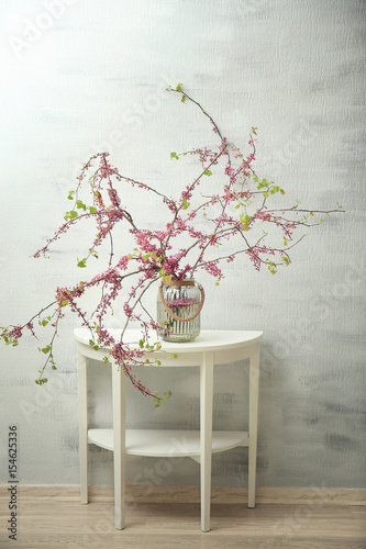 Glass Vase With Branches Of Blooming Tree Flowers On Table Stock