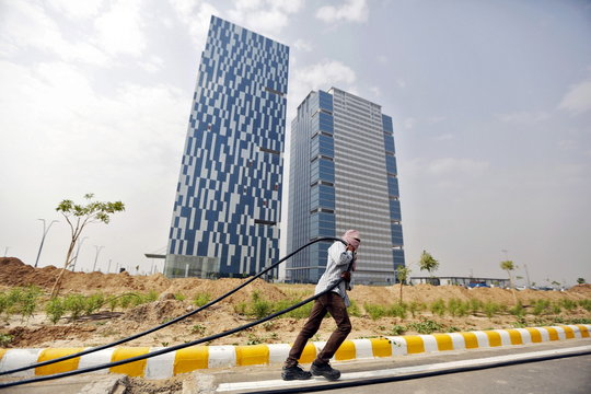 A labourer pulls cable in front of office buildings in Gujarat International Finance Tec-City at Gandhinagar