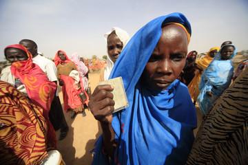 Internally displaced people wait during a food distribution at Kalma Camp in South Darfur