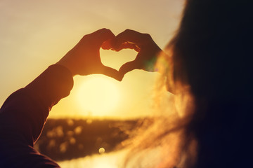 Young woman making heart with her hands at sunset
