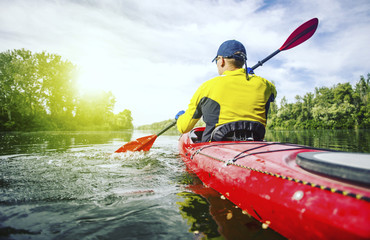 A man rafts on a kayak on the river in a sunny day.
