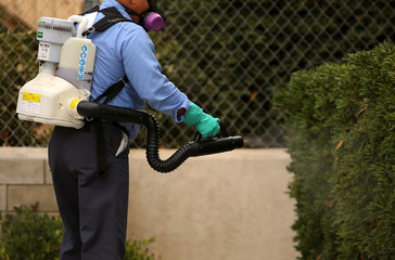 A county vector control member hand-sprays a home for adult Aedes mosquitoes after a travel-related case of Zika was confirmed in this neighborhood of San Diego
