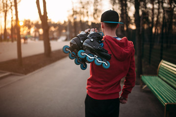 Roller skater with skates in hands, back view